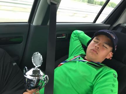 Keeper Bruno slapend met beker op zijn buik terug in de auto naar huis
